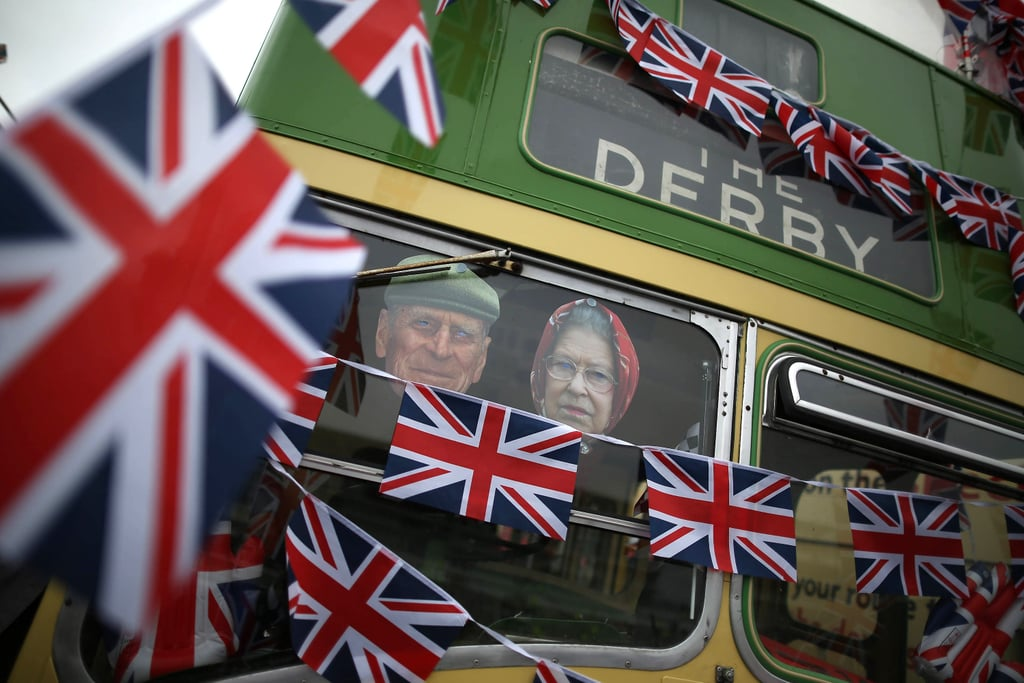 A bus is decorated with Union Jack flags and photographs of Queen Elizabeth II and the Duke of Edinburgh at the derby.
