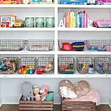 "Problem: The room is finally organized . . . for now. But kids grow, change interests, and keep getting gifts. Ugh, there's just no way to stay on top of it. Solution: Yes, there is! ""Use large baskets to accommodate bulky categories like stuffed animals, blocks, and train sets,"" they said. ""For the smaller and more specific categories, use stackable shoe boxes and a paint pen to identify each item. The paint pen easily wipes clean with rubbing alcohol for future updating!"" The experts also use dry erase tape for less-permanent labeling. Another tip is to make it a house rule that the toy can only stay if it's been played with that past year. ""According to our kids, they've played with all of their toys . . . which we know isn't true."" Problem: Real talk: not everything fits in a bin! Solution: As much as Clea and Joanna love themselves a good bin or basket, even they acknowledge it's not the answer to everything. For things that don't fit on a shelf — like play tables, ride-along toys, or dollhouses — there's hope. They swear by the ""one in and one out"" philosophy, which means you donate one large, bulky toy for every large, bulky purchase. When that still doesn't help, ""Try creating zones so every space has a purpose and every item has a home,"" they said. ""If you have a lot of trucks, for instance, create a 'parking lot' so that there's a designated spot for them. The zone will hold you accountable and keep the room from descending into toy chaos."""