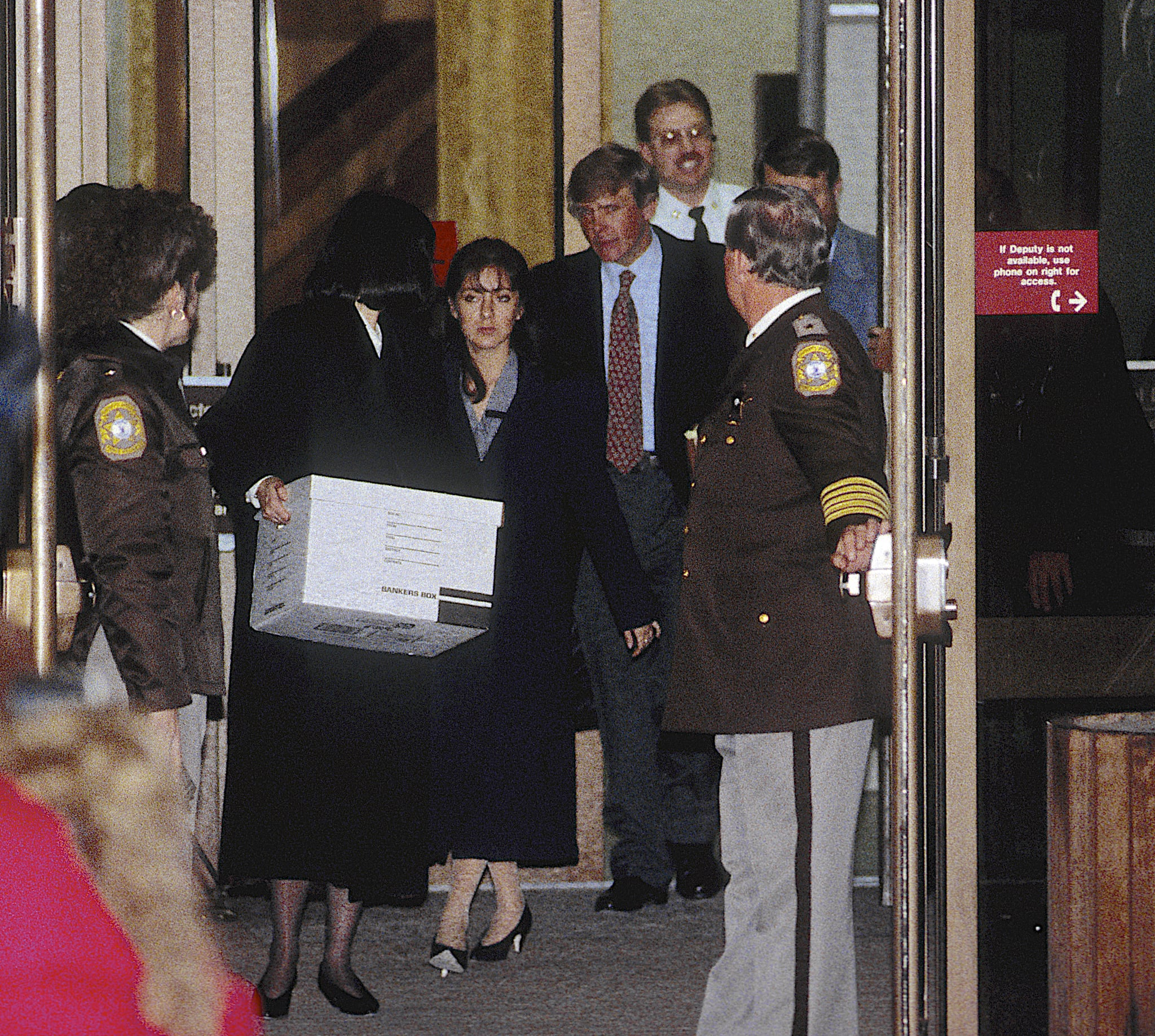On the second day of her trial, the accused, Lorena Bobbitt (centre), and her lawyers, Lisa Kemler (with box), Blair Howard (red tie), and James Lowe (right, mostly obscured behind deputy), leave the Prince William County Courthouse, Manassas, Virginia, January 11, 1994. Bobbitt was accused (and later acquitted) in the malicious wounding of her husband when she, two years earlier, had severed his penis with a kitchen knife. (Photo by Mark Reinstein/Getty Images)