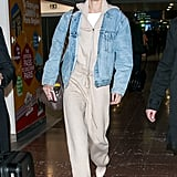 At an airport wearing a tan Sally LaPointe sweatsuit with Stuart Weitzman shoes, a Levi's denim jacket, and a Fendi duffel bag.