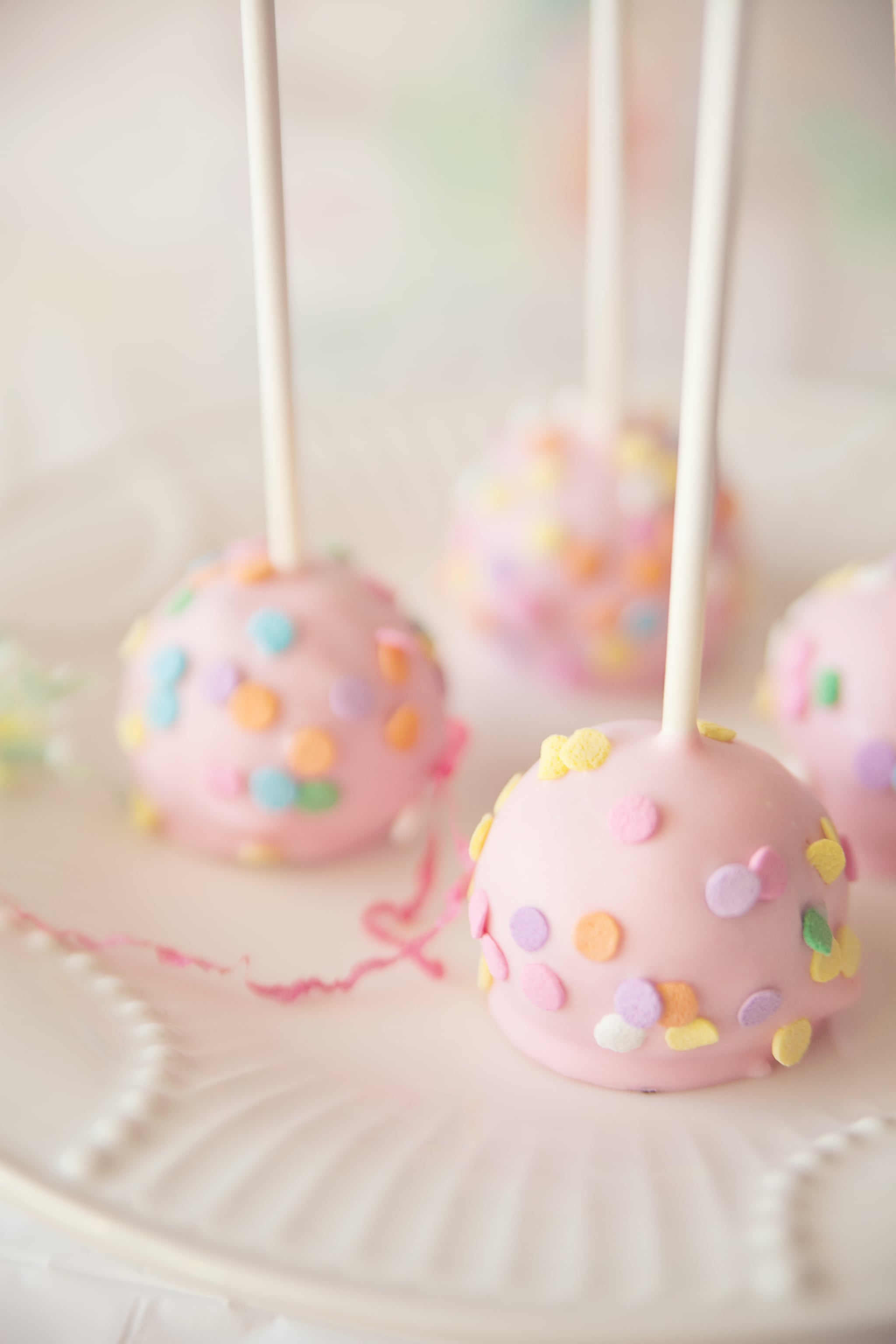 Some chocolate cake pops with pink candy coating and confetti sprinkles on plate.