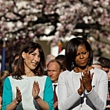 Samantha and Michelle clap on the White House lawn.