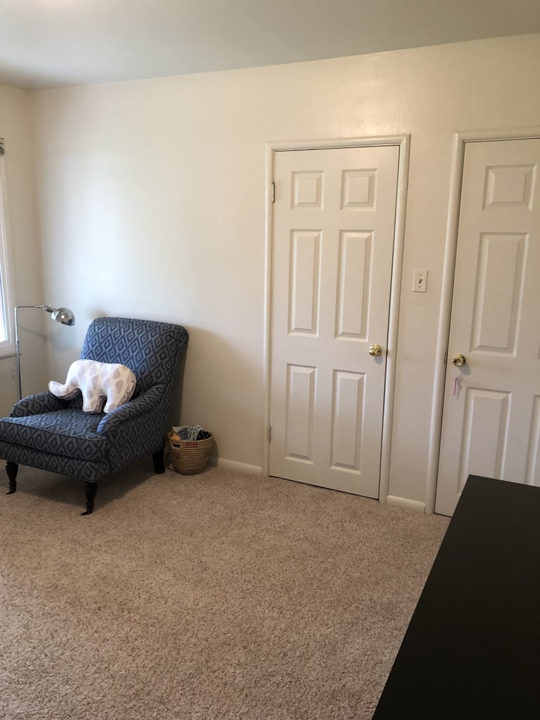 A chair, floor lamp, and small basket occupied the wall space next to the closet door.