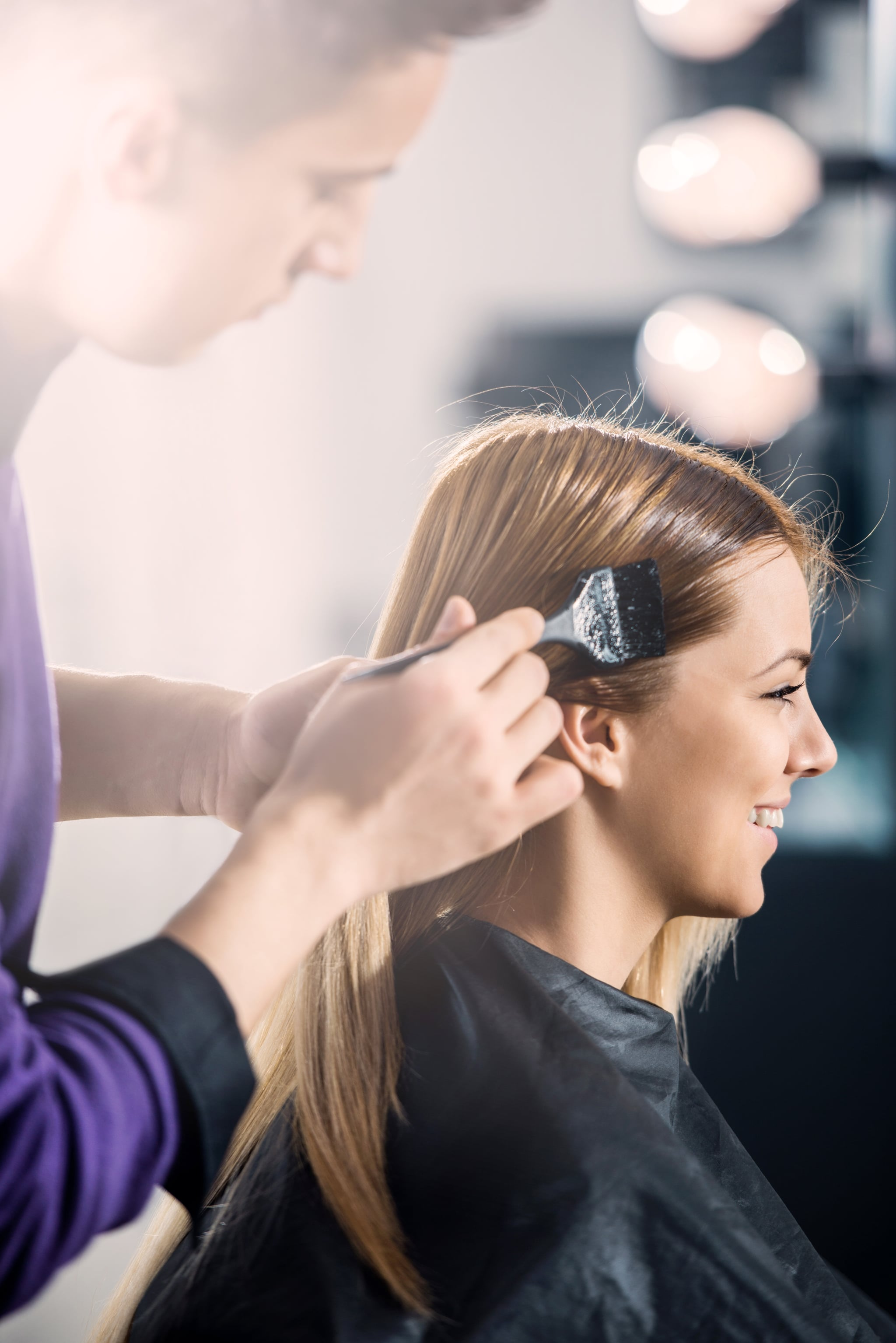 Young woman dyeing hair at the hairdresser's.