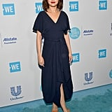 On April 19, Selena attended WE Day California at The Forum. She wore a navy wrap dress and cool structural heels on the blue carpet.