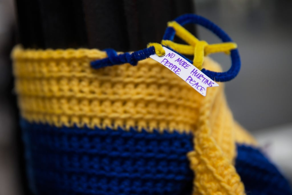 "A knitted tribute with a note — ""No more hurting people. Peace."" — hung on a street light along the Boston Marathon course."