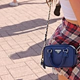 You don't often pair a blue Prada crossbody bag with a flannel tied around the waist, but we love the combination.