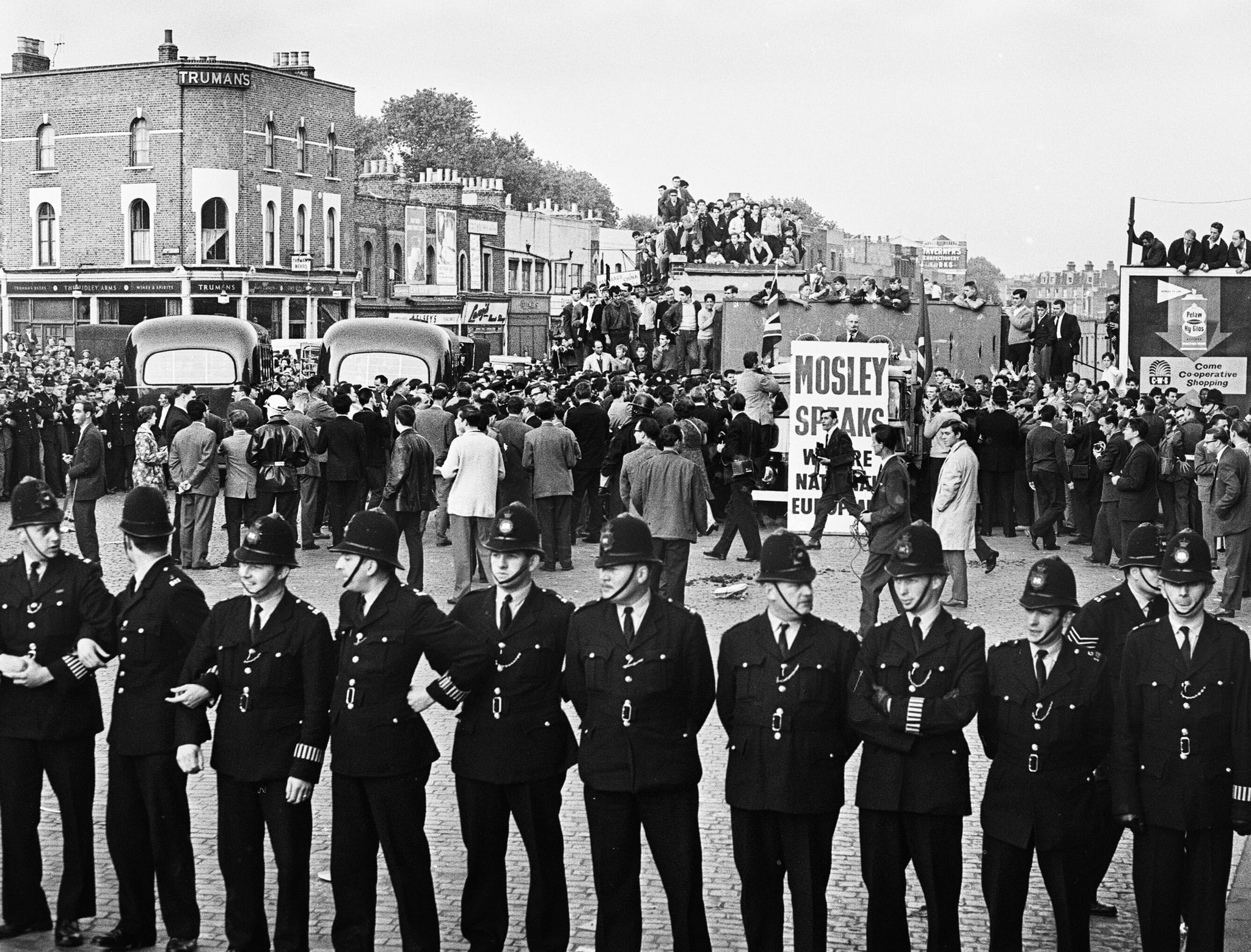 Large crowd gathered in Ridley Road E8 to demonstrate against former fascist leader Sir Oswald Mosley and members of his anti-Semitic Blackshirt group who had planned a rally in London's East End. Mosley and his anti-Semitic Blackshirt were assaulted and punched to the ground as soon as his meeting opened at Ridley Road, Dalston. Police closed the meeting within the first three minutes and made 54 arrests, one which was Sir Oswald's son Max., our picture Shows: Police presence at the rally, 31st July 1962. (Photo by Alisdair MacDonald/Mirrorpix/Getty Images)