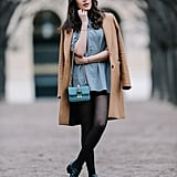 With a Long Flowy Top, Shorts, a Camel Coat, and Black Ankle Boots