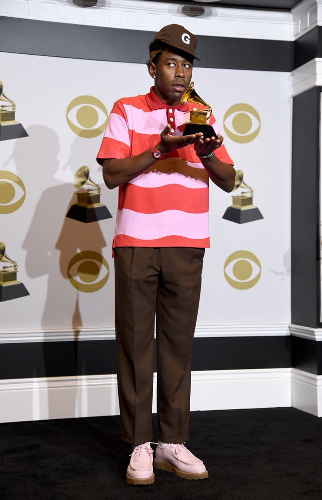 "Tyler, the Creator's style is very distinct, much like his music. It's hard to forget his 2020 Grammys outfit that sparked a thousand memes. Tyler paid homage to Wes Anderson's The Grand Budapest Hotel in a pink bellboy outfit from his brand Golf le Fleur. The alternative rapper completed his intriguing outfit with a matching hat, white oxfords, gloves, square sunglasses, and a suitcase filled with clothing. The ""Earfquake"" singer then went on to switch into a two-toned pink and red suit while putting on a mesmerizing performance on stage — that's just the magic of Tyler.  Much like his performances, Tyler's fashion sensibilities are also one of a kind. He has a way of owning a red carpet look consisting of a bucket hat, sweater vest, and a pair of shorts. Clearly, his amazing style hasn't gone unnoticed, since he's teamed up with both Lacoste and Converse for highly sought after collaborations. While the rapper is known for his streetwear looks, he also isn't afraid to give high-fashion outfits a try. During the 2018 Grammys, Tyler wore an icy blue Louis Vuitton look that took everyone by surprise. Ahead, we've compiled a list of 20 of our favorite fashion moments from Tyler.      Related:                                                                                                                                Tyler, the Creator Eloquently Breaks Down Why Grammys Voting Is Unfair After His First Win"