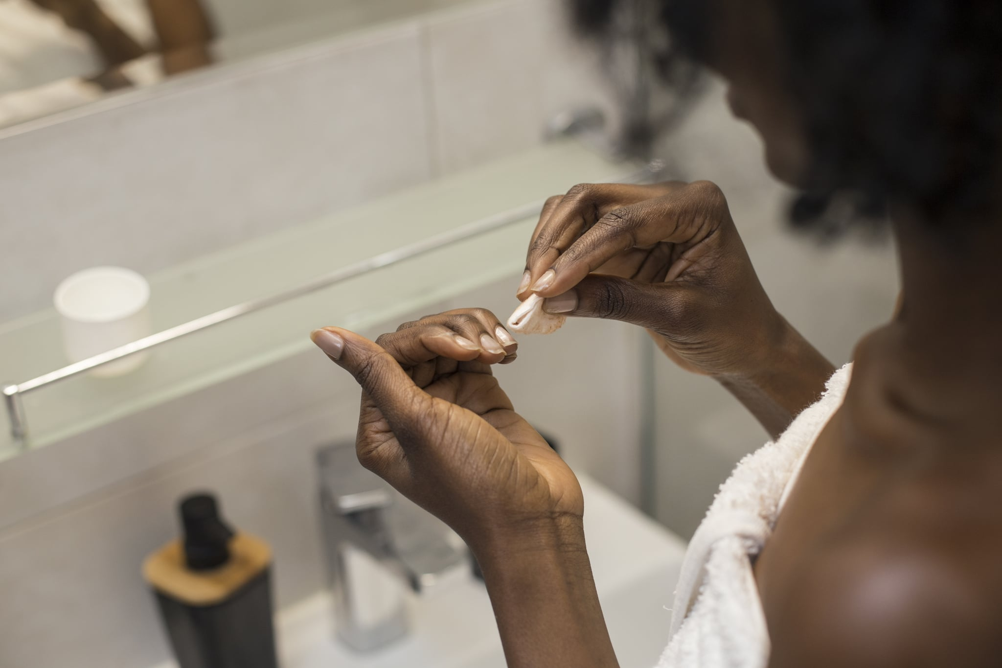 Unrecognizable African female removing her nail polish.
