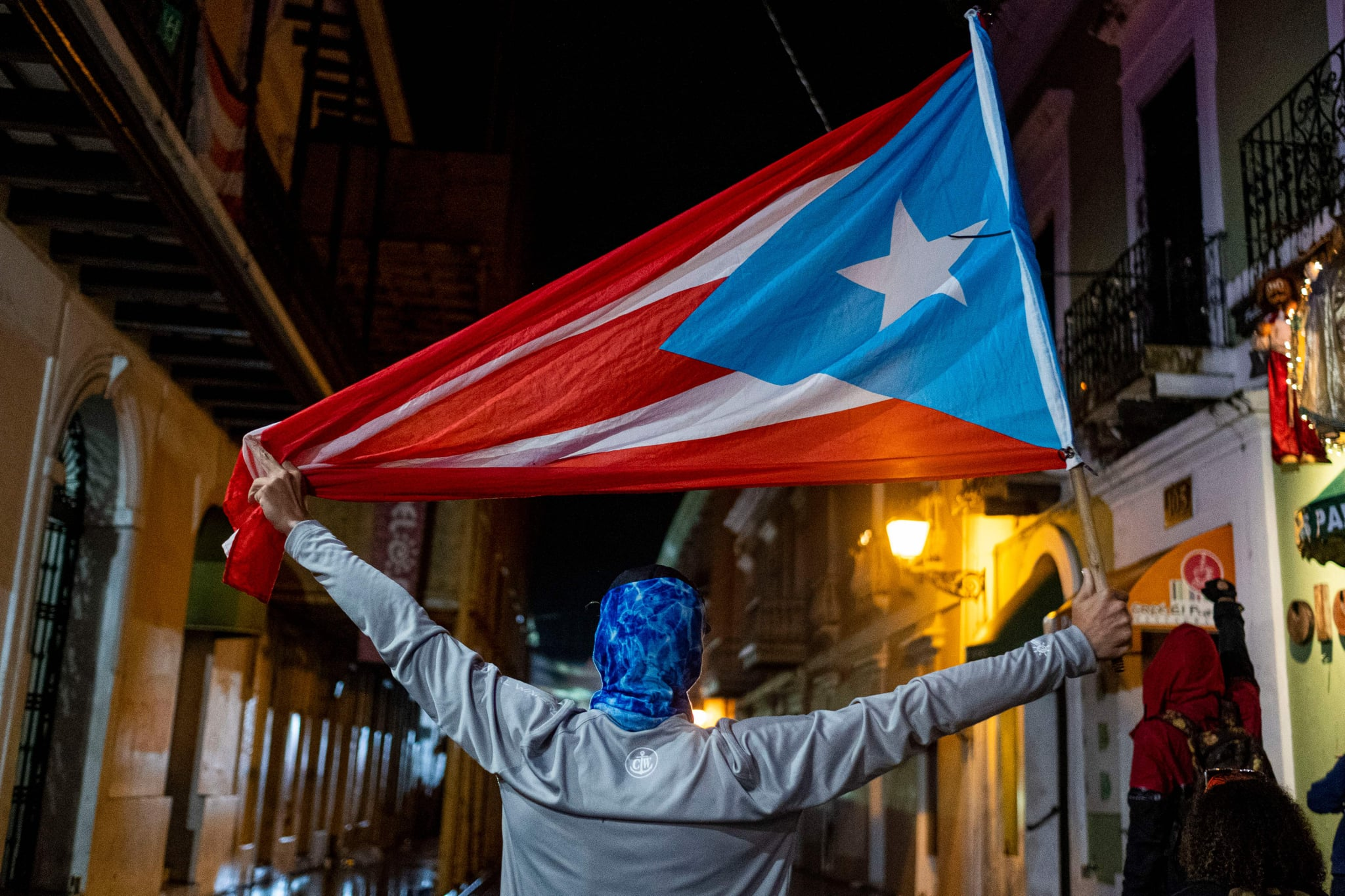 TOPSHOT - A protester holds a Puerto Rican flag during a demonstration against Puerto Rico's governor and the government in front of the governor's mansion in San Juan, Puerto Rico on January 23, 2020. - Residents are protesting after a warehouse full of relief supplies, reportedly dating back to Hurricane Maria in 2017, were found having been left undistributed to those in need. (Photo by Ricardo ARDUENGO / AFP) (Photo by RICARDO ARDUENGO/AFP via Getty Images)