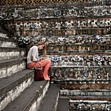 A tourist read on the steps of a temple in Bangkok, Thailand.