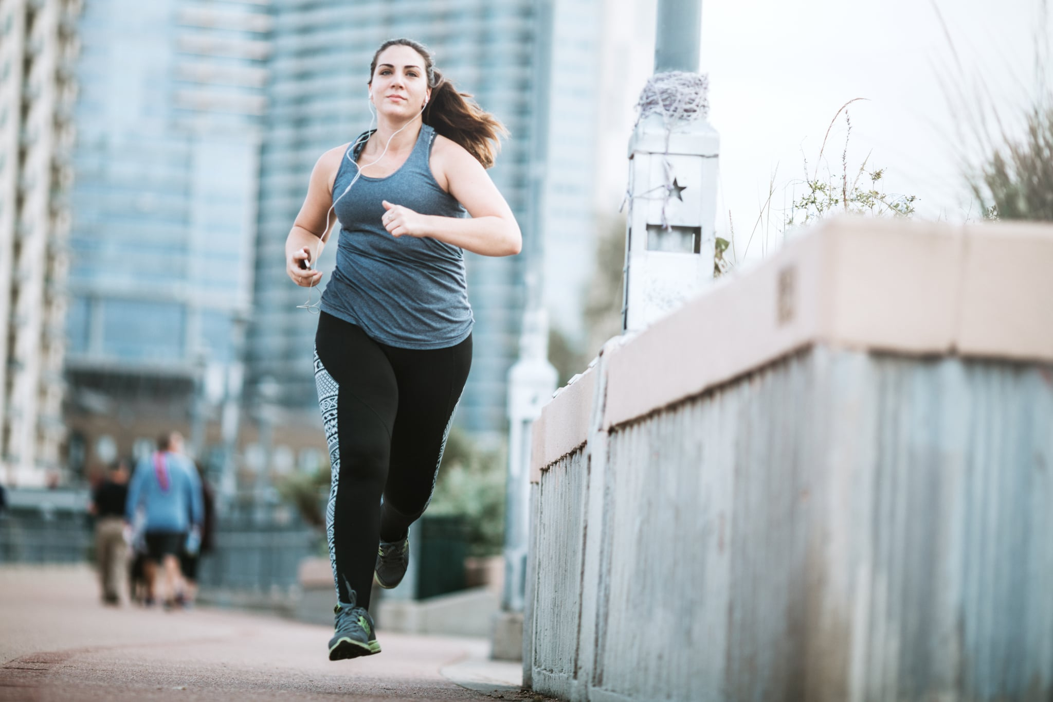 A young adult woman goes for a morning run, crossing the Lamar Street pedestrian bridge in Austin, Texas.  The bridge gets a large volume of foot traffic in the morning with people exercising at the start of their day.  She has a focussed look of determination, listening to music on her smartphone.