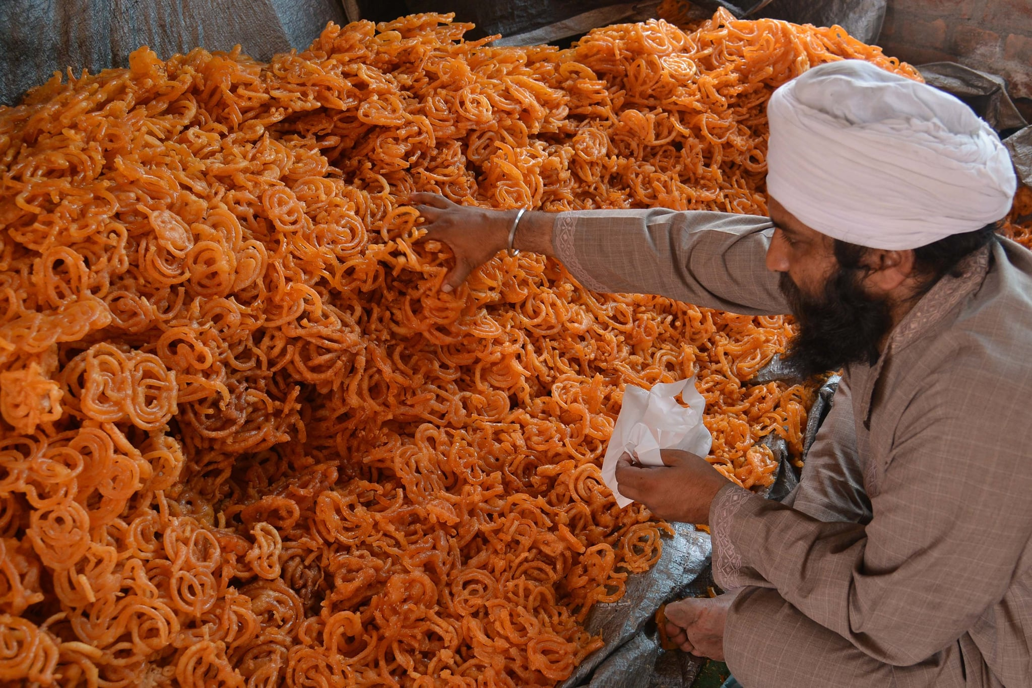 An Indian Sikh devotee puts 'Jalebi' sweets in plastic packets for free distribution to devotees during the Baisakhi festival celebrations held at Langar Ghar, a community hall at the Golden temple in Amritsar on April 14, 2015. Baisakhi, which is celebrated in the Punjab region, coincides with other festivals celebrated on the first day of Vaisakh, in some regions of India such as Puthandu, the Tamil New Year.  Baisakhi is especially important for the Sikh community as it marks the establishment of the Khalsa.  AFP PHOTO / NARINDER NANU        (Photo credit should read NARINDER NANU/AFP via Getty Images)