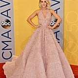 On the red carpet, Carrie Underwood wore a Michael Cinco gown encrusted with Swarovski crystals, pearls, and scattered organza flowers. She accessorized with Butani diamond earrings, a Hearts on Fire diamond ring, and a Harry Kotlar diamond ring.