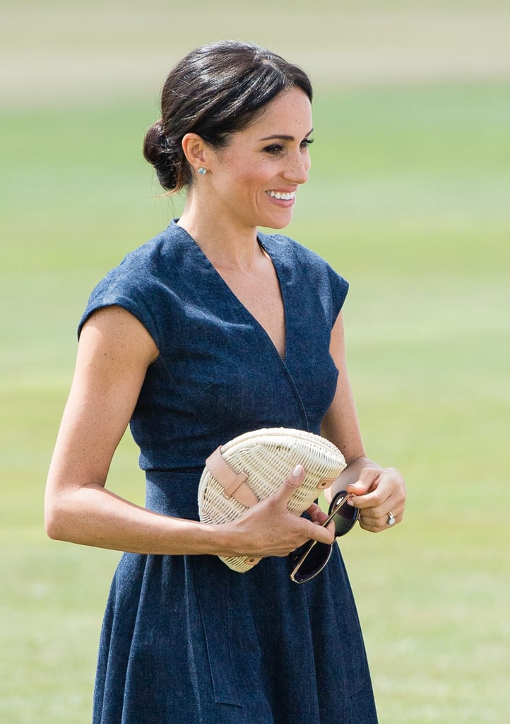 Meghan accessorised her denim Carolina Herrera dress with a raffia J.Crew clutch at the Sentebale Polo in Windsor in 2018.