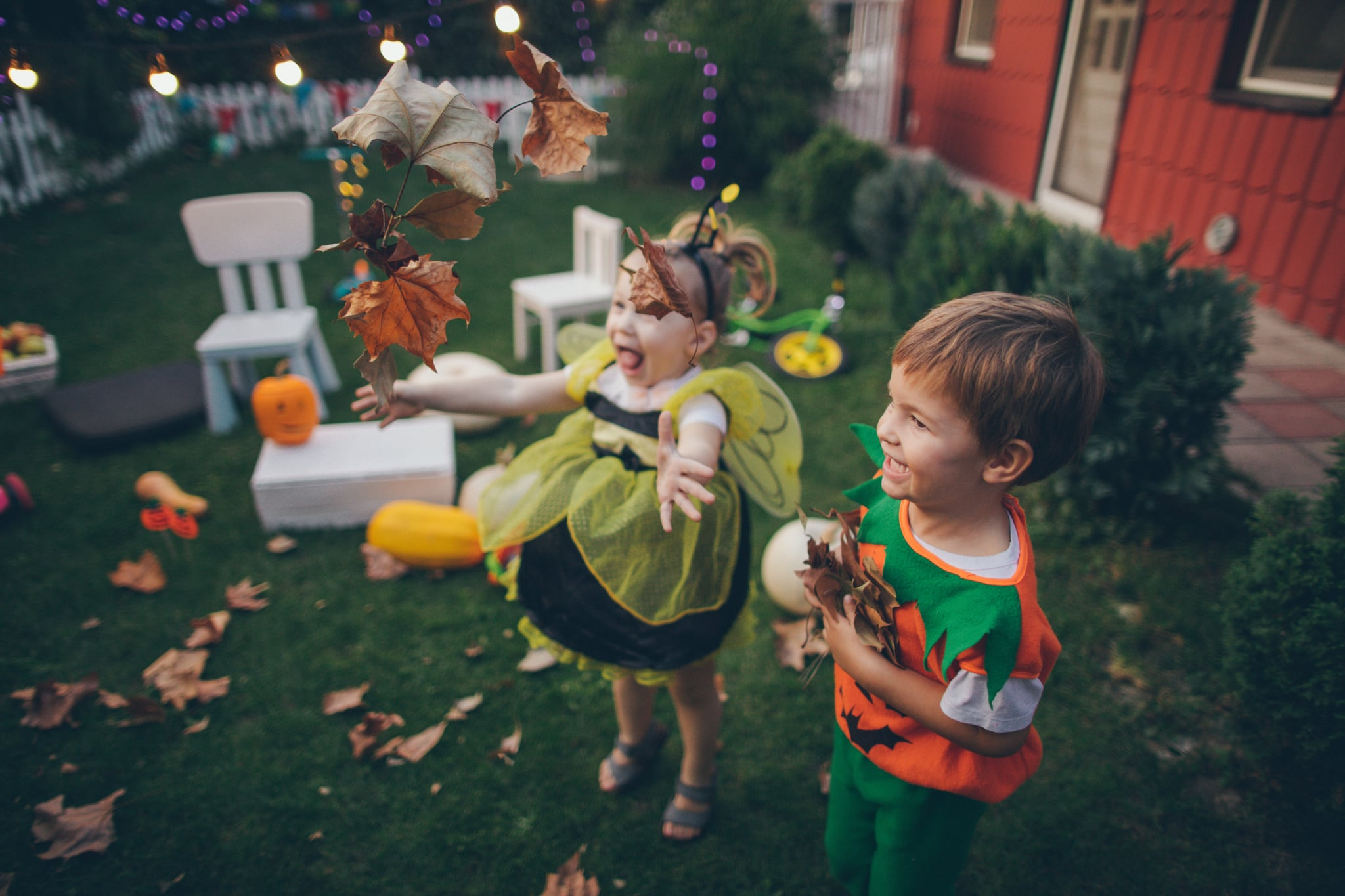 Little boy and little girl having fun in the backyard during the Halloween