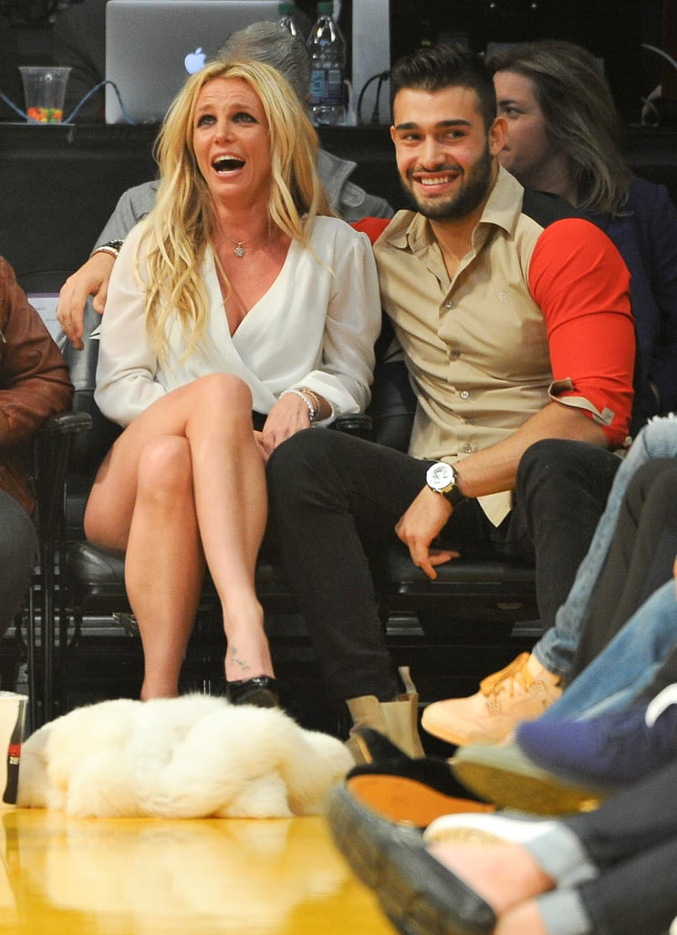 "Britney Spears took a break from her run of Piece of Me shows in Vegas to watch the Los Angeles Lakers play the Golden State Warriors in LA on Wednesday, and she wasn't alone. Along with her two sons, Sean and Jayden Federline, Britney also brought along boyfriend Sam Asghari, a dancer she's been dating for over a year. While sitting courtside, Britney and Sam were projected on the big screen for the Kiss Cam, and the singer got adorably flustered before leaning in to give Sam a smooch. Britney and Sam met in 2016 while working together on her ""Slumber Party"" video, and the 23-year-old has made a handful of appearances on Britney's Instagram feed. Keep reading to see their cute courtside date, then read up on all the other men Britney has wooed over the years."