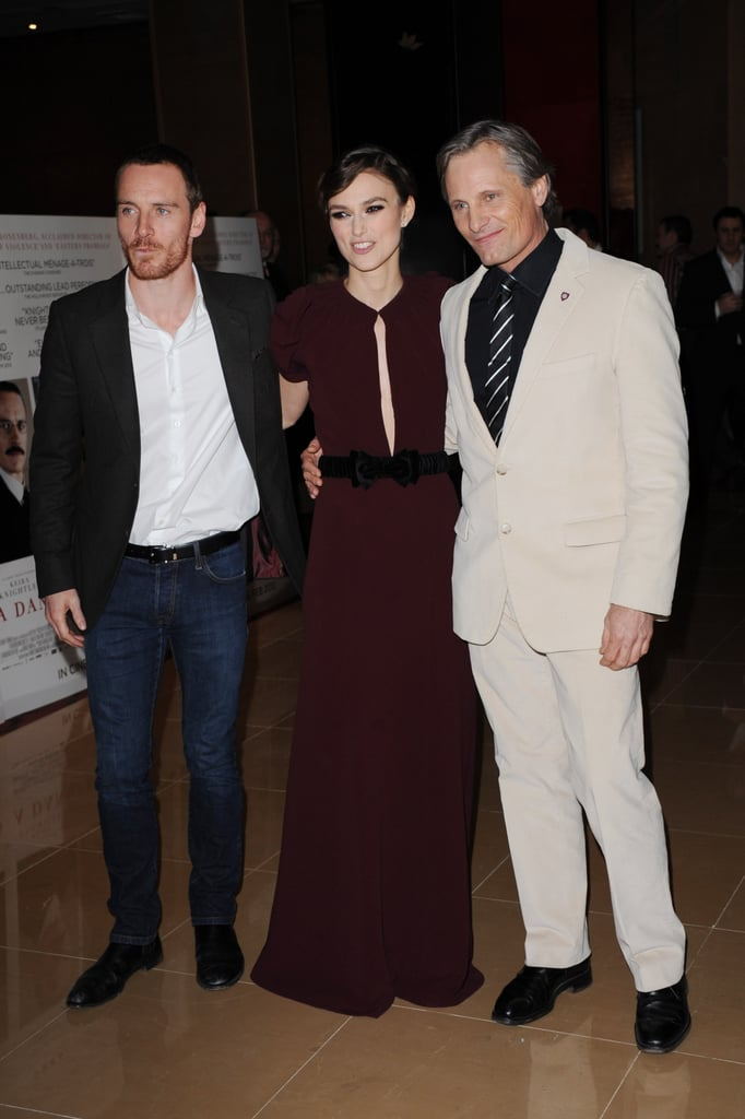 "Michael Fassbender reunited with his A Dangerous Method costars Keira Knightley, in Burberry Prorsum, and Viggo Mortensen this evening for a London premiere. The film came out in the US last Fall but is only just hitting theaters in Keira's home country. To promote the release, Keira's on the cover of GQ UK. An interview in which she discusses making the sex-themed David Cronenberg picture accompanies an equally racy photo spread. Speaking about her relationship with Klaxons musician James Righton and a recent reimmersion in work, Keira said she's in a great place. She commented, ""I'm actually loving this bit right now — doing the work I'm doing, having the life I can have around it. Right now, it's really good.""  We recently caught up with Keira to find out what she thought about working with Michael. Many thought Michael was overlooked when he didn't snag an Oscar nomination for his role in Shame, and Keira likely agrees. She told us of Michael's performance in Shame, ""I think he's amazing . . . He's a phenomenal actor, and I think his performance in Shame is amazing. Talk about brave. I think it's wonderful."""