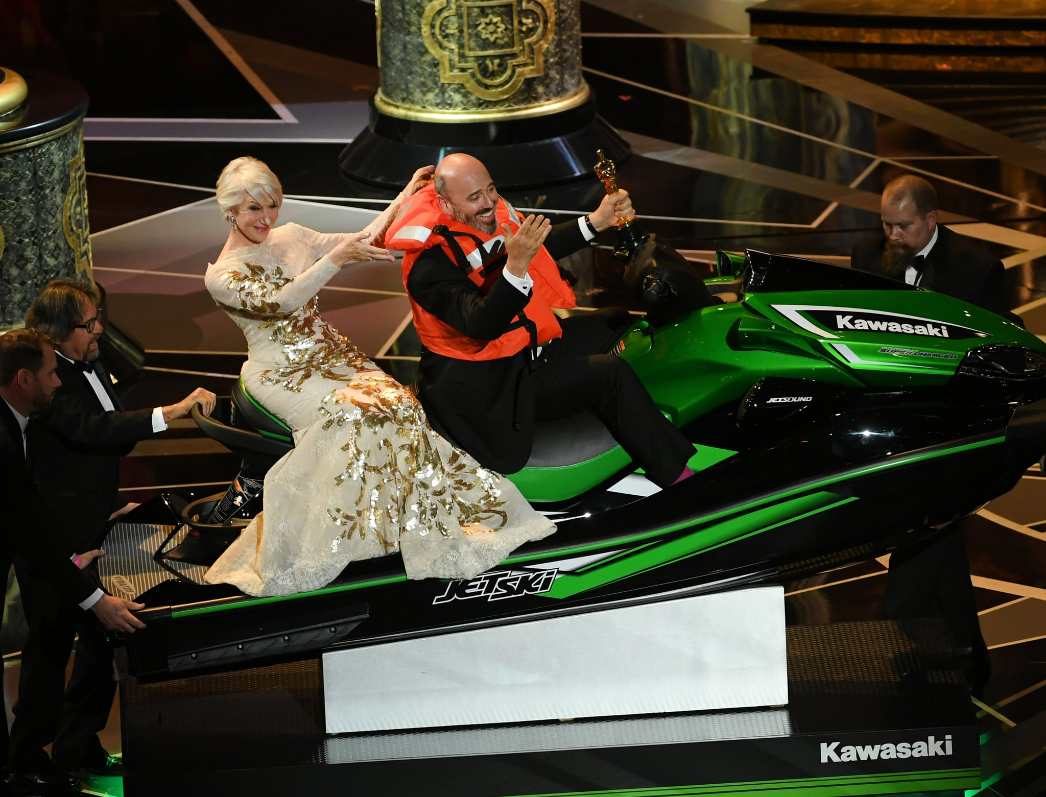 HOLLYWOOD, CA - MARCH 04:  (L-R) Actor Helen Mirren with Oscar-winning costume designer Mark Bridges sitting on a Jet Ski (which he received as a prize for shortest acceptance speech) onstage during the 90th Annual Academy Awards at the Dolby Theatre at Hollywood & Highland Center on March 4, 2018 in Hollywood, California.  (Photo by Kevin Winter/Getty Images)