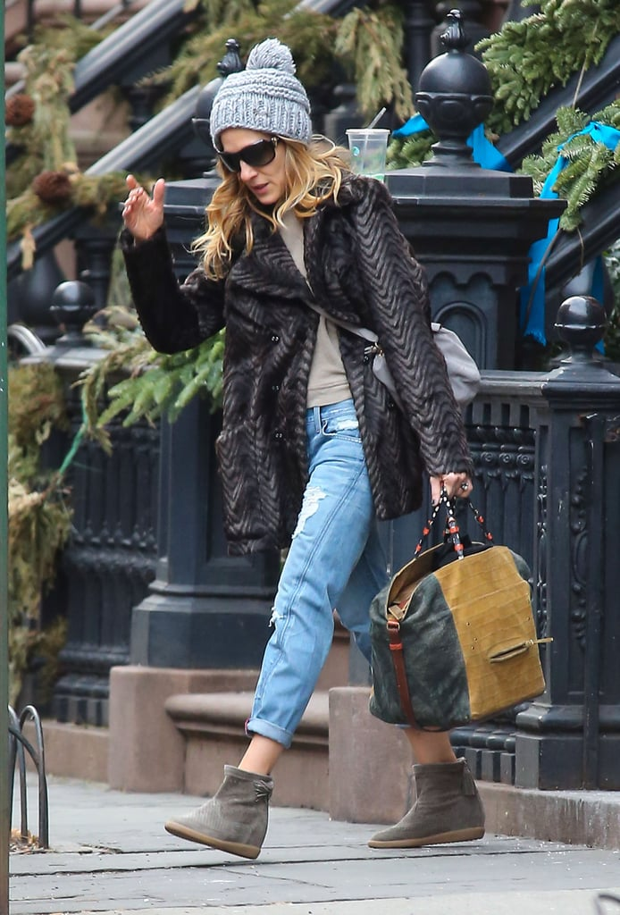 Sarah Jessica Parker headed out of her NYC apartment in a layered-up outfit, including a gray knit beanie, fur coat, ripped boyfriend jeans, and Isabel Marant booties.