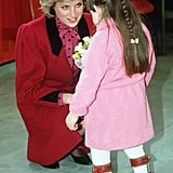 In March 1986, Diana crouched down to talk with a young girl wearing leg braces in London.