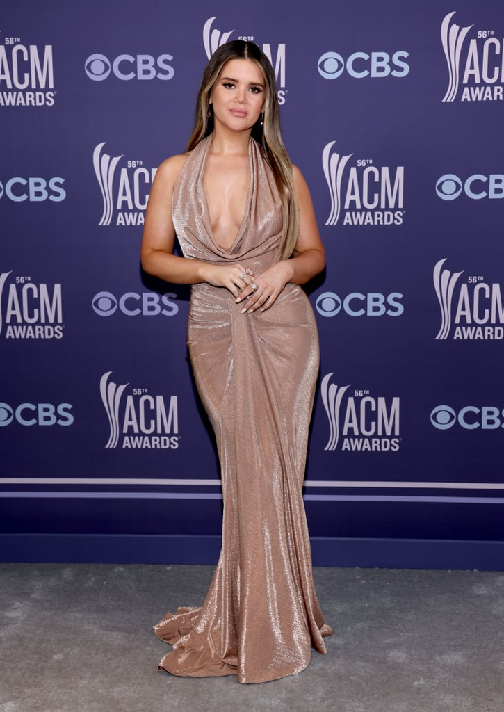 Maren Morris sparkled at the ACM Awards, both in the literal and figurative senses. The country singer attended the award show on Sunday wearing a glimmering rose-gold gown that resembled a crisp glass of Champagne in the best way possible. By the brand LBV and priced at $3,275, the glamorous dress featured a draped sarong silhouette with a slight train.  Maren, who performed a romantic duet with her husband, Ryan Hurd, kept her accessories simple, opting for matching rose-gold earrings and rings and Stuart Weitzman shoes. In fact, Maren's best accessory may have been her cursive back tattoo, which was perfectly framed by the dress's halter neckline. See the red carpet look from all angles ahead.      Related:                                                                                                           Carrie Underwood Looked Like a Monarch Butterfly in Her Mesmerizing Latin AMAs Dress