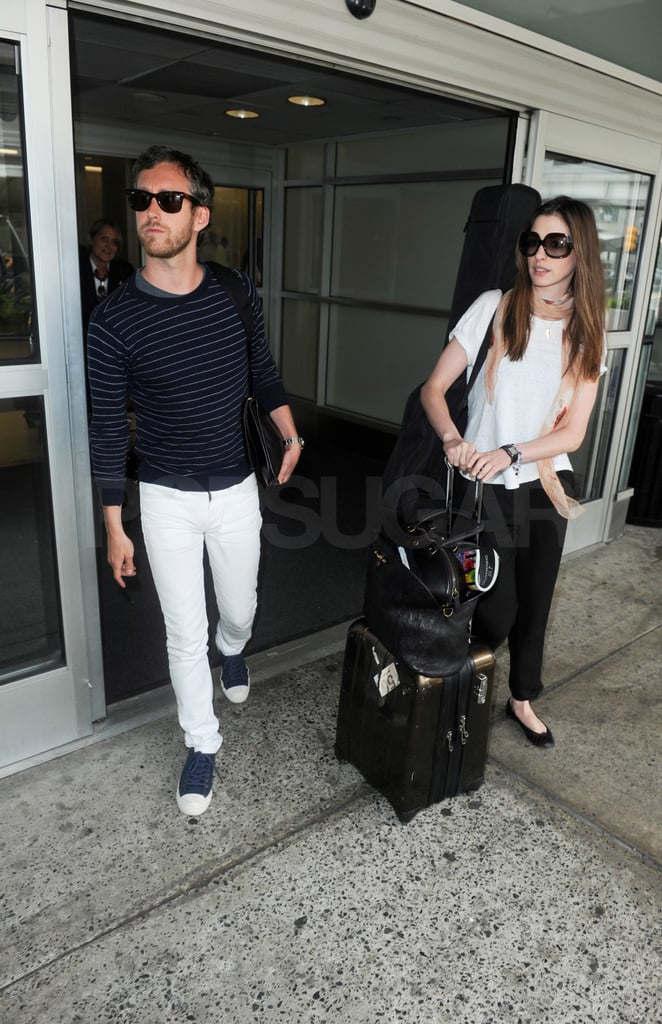 Anne Hathaway and Adam Shulman rolled their luggage out of JFK.
