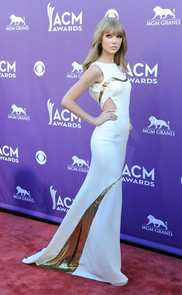 Taylor Swift showed off her more mature side in a daring cutout J. Mendel gown on the red carpet at the ACM Awards in Las Vegas this evening. It's been a busy weekend of honors for Taylor, who accepted the Big Help blimp at Saturday's Kids' Choice Awards in LA. Michelle Obama actually presented to Taylor during that show, and the two first daughters, Sasha and Malia, got to come along for the fun. Taylor is up for multiple awards at today's show, though; unfortunately the fan she was supposed to have along as her date was unable to come at the last minute.  New Jersey high school senior Kevin McGuire invited Taylor to his prom, but instead she planned to bring him along to the ACMs. Sadly, Kevin, who is battling leukemia, was admitted to the hospital on Friday and couldn't make the trip, though Taylor tweeted that she'll make it up to him in another way.