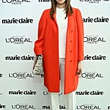 Her all-white separates got a major boost from an oversize clutch and a crisp, neon coat.
