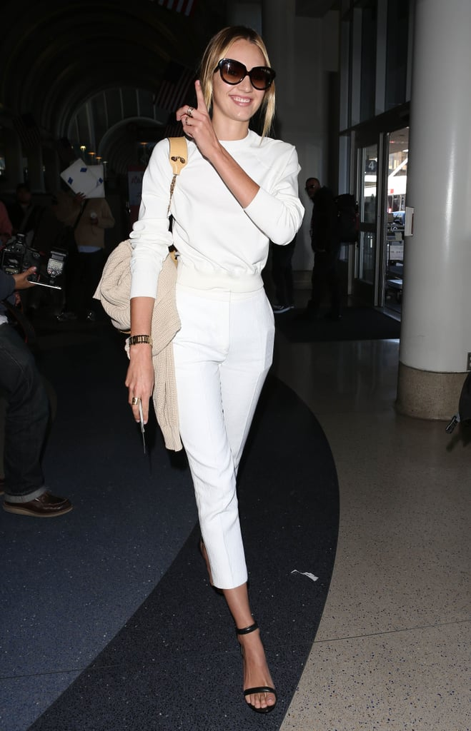 "Candice Swanepoel worked all-white the practical way with a fitted top and high-waisted trousers — then added a pair of ankle-strap heels for a look that says ""frequent flier-meets-Summer-styler."""