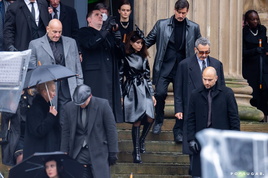 While we got our first glimpse of Zoë Kravitz's Catwoman in The Batman trailer, we're finally getting to see what she looks like as her alter ego, Selina Kyle. On Oct. 12, Kravitz was spotted filming in the UK, dressed head to toe in black and accompanied by John Turturro as mobster Carmine Falcone. Judging from the photos, it seems Selina attends the same funeral previously seen in the trailer.  In an iteration of the comics, Selina is the daughter of Carmine, and the expensive look of her outfit coupled with the fact she's leaving the funeral with him suggests that this may be a plot point visited in the upcoming film. Sadly, we'll have to wait until March 4, 2022, to have our The Batman questions answered, but until then, bask in the glory that is Kravitz as Catwoman.       Related:                                                                                                           Meet the Stars Joining Robert Pattinson in Matt Reeves's The Batman