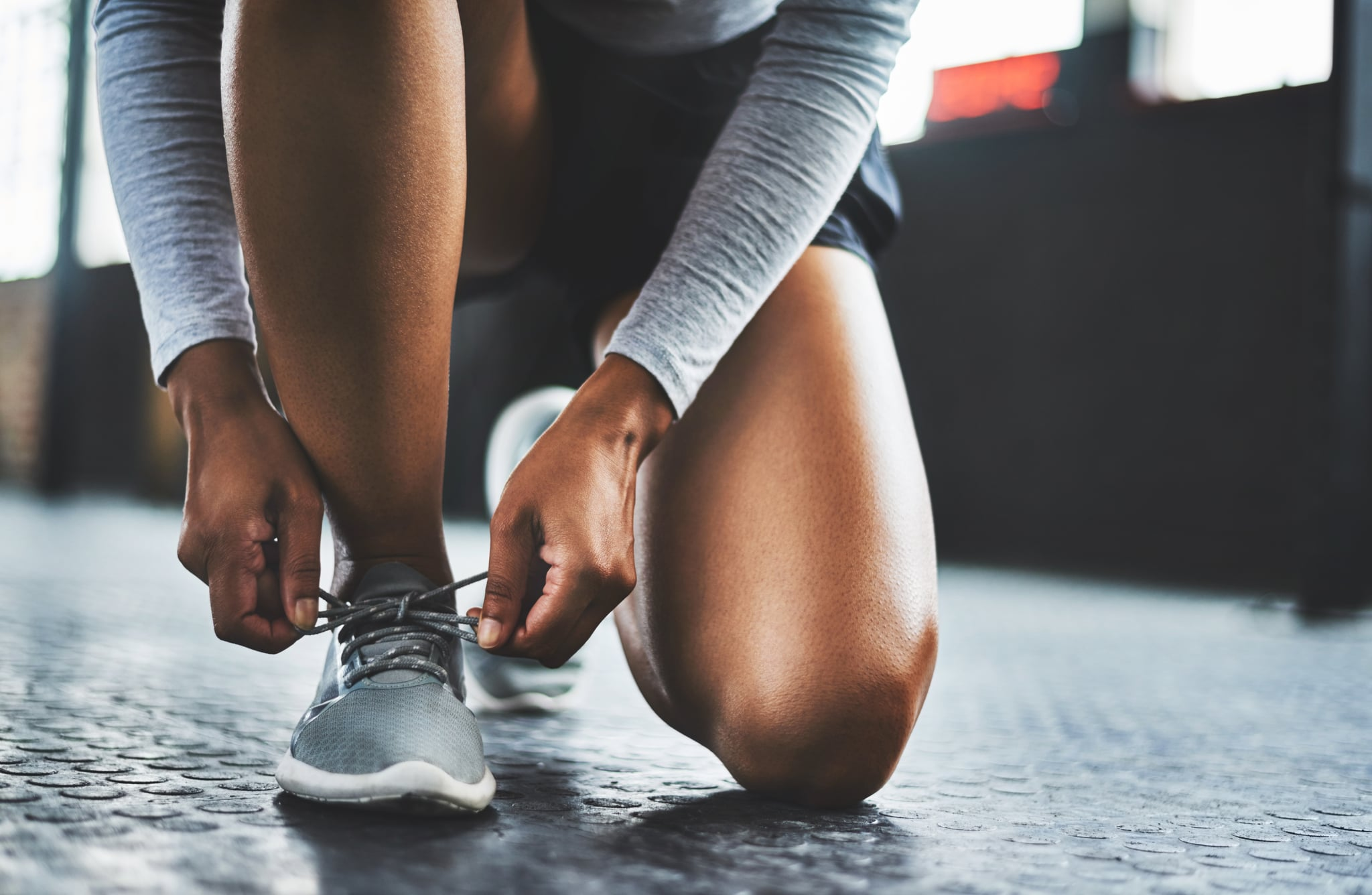 Cropped shot of a woman tying her shoelaces in a gym
