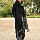 Binx Walton Left the Alexander McQueen Show in Striped Trousers, a Black Coat, and an Oversize Scarf