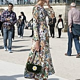 A sweet daisy-adorned bag echoes the pretty florals on her dress.