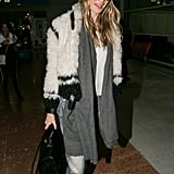 Behati Prinsloo nailed Winter travel style in the coziest of ensembles wearing a knit hat, gray scarf, denim, and a furry crop coat.