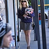 This may be our favorite Reese Witherspoon look yet — the actress looked fresh and pretty in a heart-print sweater, gray skirt, and ankle booties, then added a cool factor via a sleek gray hat and Ray-Bans.