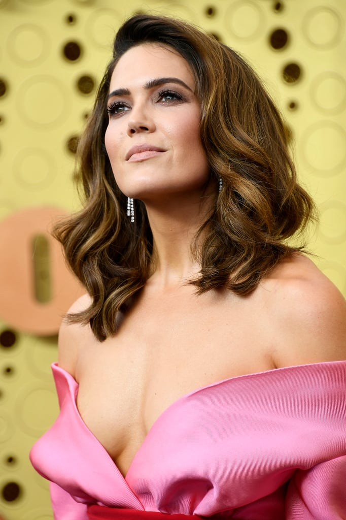 Mandy Moore turned up the volume for the 2019 Emmys. The This Is Us actress, who is up for her first-ever Emmy nomination for outstanding lead actress in a drama series, appeared at the award show with glamorous, va-va-voom hair. Though the hairstyle felt reminiscent of the 1960s, hairstylist Ashley Streicher said she was actually inspired by '90s supermodels, specifically Cindy Crawford. For her makeup, Moore went with a taupe smoky eye, bold brows, and a neutral lip. The feminine look paired well with her pink-and-white Brandon Maxwell gown. Get a closer look at Moore's timeless hair and makeup ahead.      Related:                                                                                                           No Big Deal, Just Jameela Jamil Revealing She Did Her Own Makeup For the Emmys