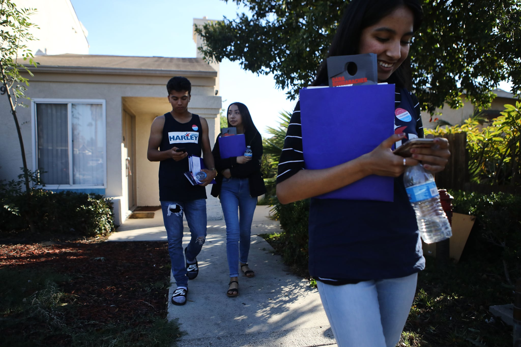 COSTA MESA, CA - OCTOBER 20:  First-generation American volunteers canvass for Democratic congressional candidate Harley Rouda (CA-48) on October 20, 2018 in Costa Mesa, California. They said they are canvassing because their parents are not allowed to vote in the election due to lack of citizenship. Rouda is competing for the seat against Republican incumbent Rep. Dana Rohrabacher. Democrats are targeting seven congressional seats in California, currently held by Republicans, where Hillary Clinton won in the 2016 presidential election. These districts have become the centrepiece of their strategy to flip the House and represent nearly one-third of the 23 seats needed for the Democrats to take control of the chamber in the November 6 mid term elections.  (Photo by Mario Tama/Getty Images)