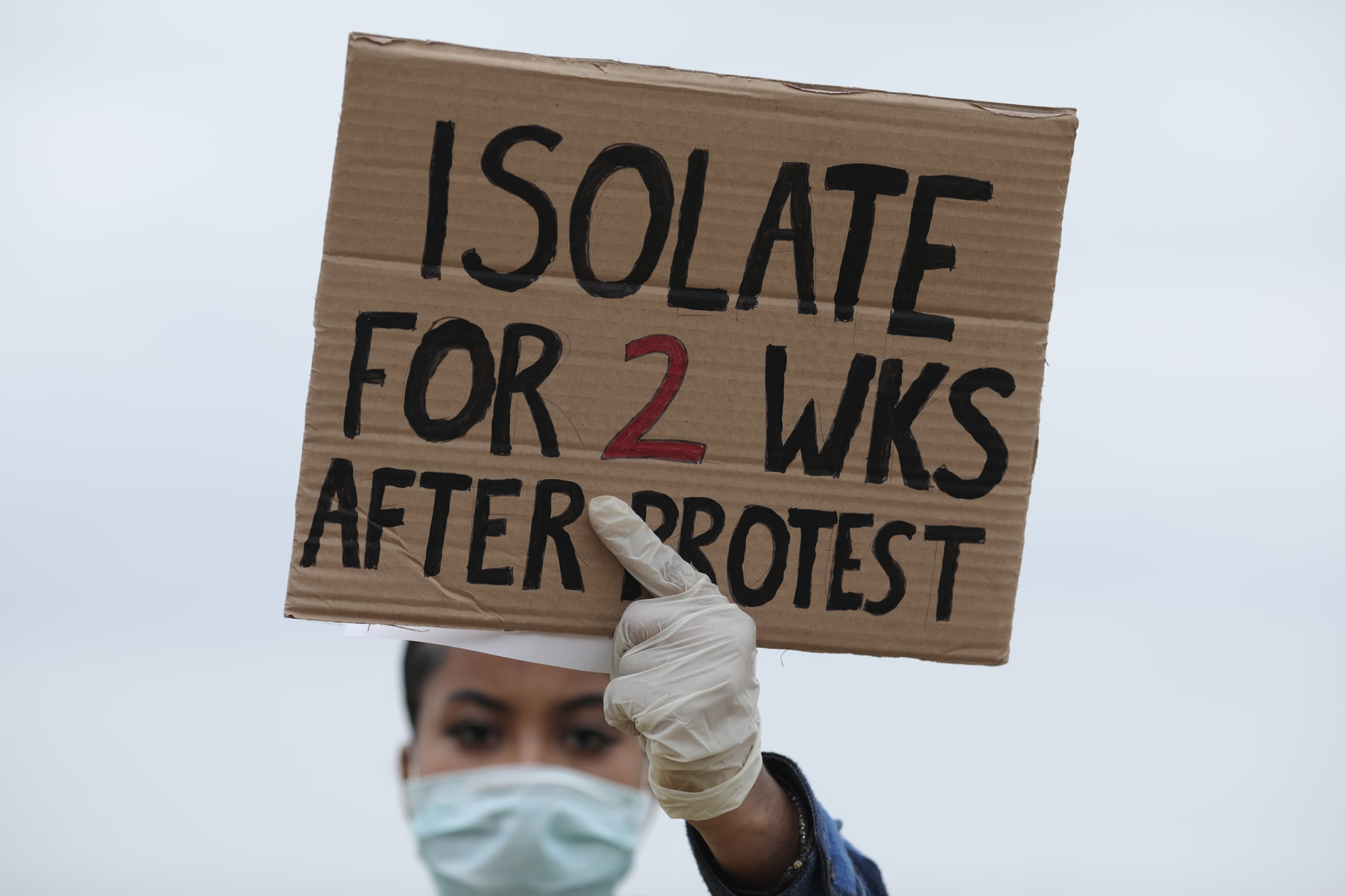 LONDON, ENGLAND - JUNE 03: A protester wearing a face mask holds up a sign saying 'Isolate for 2 weeks after protest' during a Black Lives Matter protest in Hyde Park on June 3, 2020 in London, United Kingdom. The death of an African-American man, George Floyd, while in the custody of Minneapolis police has sparked protests across the United States, as well as demonstrations of solidarity in many countries around the world. (Photo by Dan Kitwood/Getty Images)