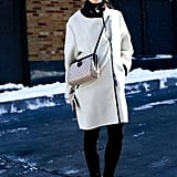 Winter whites not only match your snowy terrain, but in a minimalist cut like this car coat style, it's absolutely timeless.