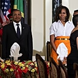 During an official dinner in Tanzania, Michelle Obama tucked a crisp white short-sleeved Zero + Maria Cornejo blouse into a striped orange skirt, then added shine via a gold belt and hoop earrings.
