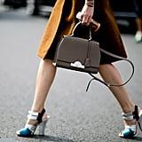 Caroline Issa carried a classic handbag — but stomped around in statement heels.