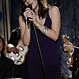 Performing in a purple dress and silver bangles.