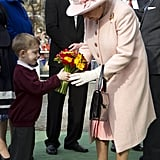 The queen accepted flowers from a young boy as she arrived at Manchester's town hall.