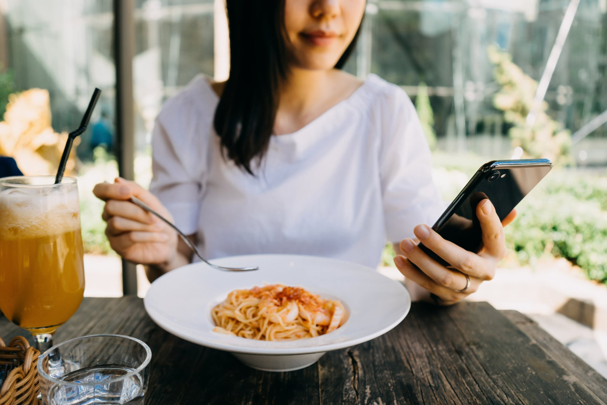 Smiling woman using her mobile phone while having meal at a cafe outdoors