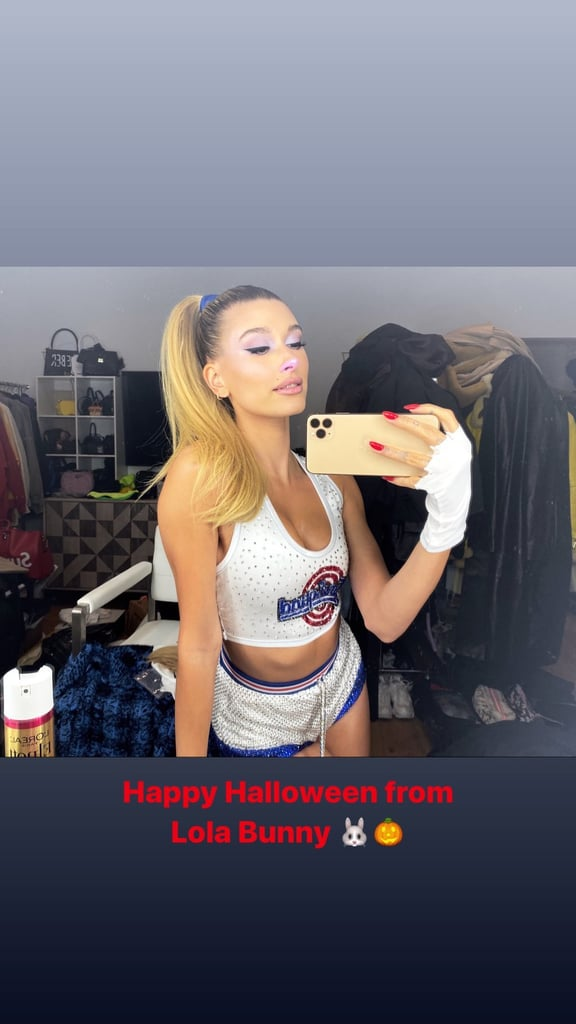 """Hailey Baldwin went the nostalgic route for Halloween this year. The supermodel dressed up for Kendall Jenner's 24th birthday party as one of our favorite '90s cartoon characters. For the bash, Hailey went as Lola Bunny from the classic 1996 movie Space Jam. She danced the night away with fellow pals like Kourtney Kardashian; Gigi Hadid, who dressed up like Jim Carrey's character from The Mask (another classic movie!); and Kacey Musgraves, who went as a Dallas Cowboys cheerleader. For the event, Hailey's stylist Maeve Reilly helped transform Hailey into the perfect Lola Bunny. She sported a pair of white shorts that were covered with tiny rhinestones and had a fluffy bunny tail on the back. She styled the shorts with a cropped basketball jersey that had the words """"Tune Squad"""" written on it and was also covered in rhinestones. To complete her costume, Hailey painted the tip of her nose pink and pulled her hair up into a high ponytail, which she tied with a blue ribbon. She also carried a towel around her neck and wore white gloves. Keep reading to see all angles of Hailey's amazing Halloween costume.  Related: See What All Your Favorite Fashion People Dressed Up as on Halloween"""