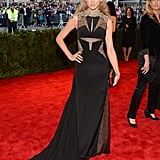 Taylor tapped into her inner punk rock princess working a gilded and laced J. Mendel gown with dark nails and a dramatic smoky eye at the 2013 Met Gala.