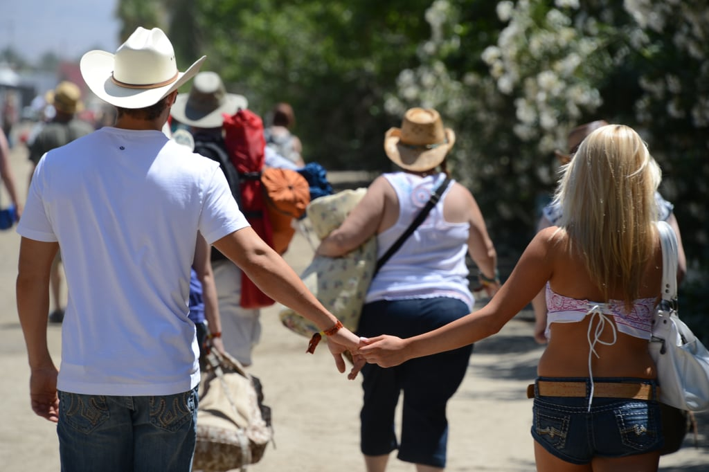 A cowboy couple held hands at Stagecoach.